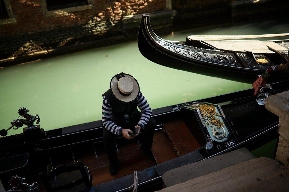 Un gondolero mira su teléfono mientras espera ser contratado por alguno de los pocos turistas que visitan Venecia desde el estallido de un brote de coronavirus. Foto del 28 de febrero del 2020.