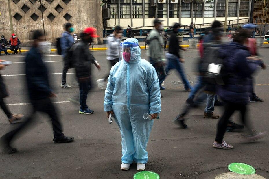 Una mujer espera afuera de una tienda con equipo de protección debido a la pandemia de COVID-19 en el centro de Lima, Perú.