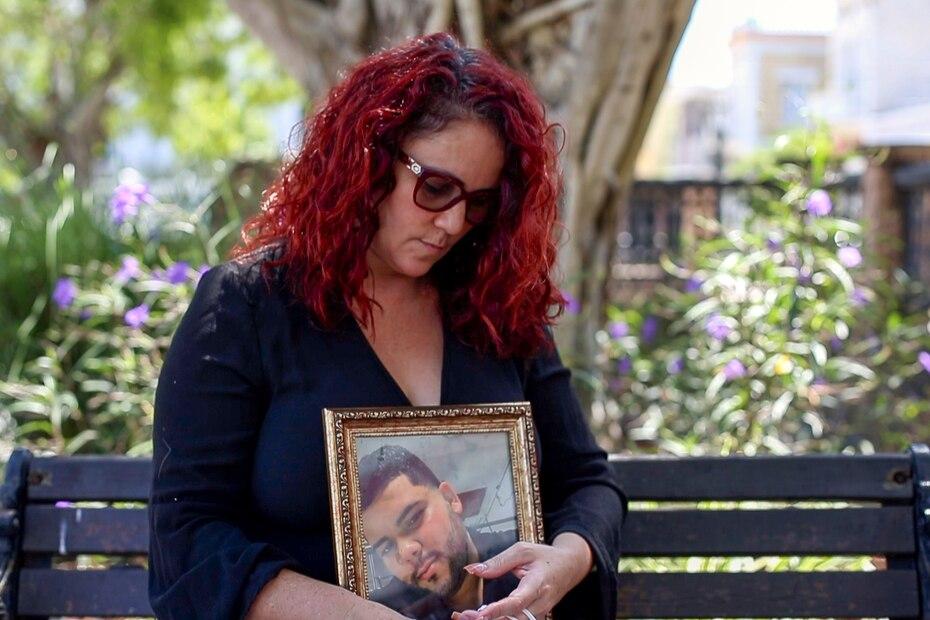 Tras la imposición de estrictas medidas para contener la propagación del COVID-19, las familias puertorriqueñas se limitaron a la sepultura de sus familiares sin un velatorio. Directrices del Departamento de Salud prohibieron la aglomeración de personas para disminuir las probabilidades de contagio. En la foto, Olga Iris González sujeta la foto de su hijo muerto por COVID-19, Ramón Francisco Rodríguez.