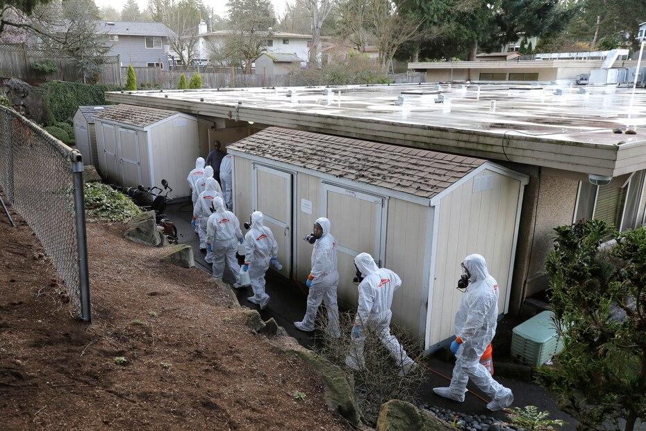 Fotografía de archivo del 11 de marzo de 2020 de empleados con equipos de protección, de la cabeza a los pies, se aprestan a desinfectar la casa de ancianos Life Care Center de Kirkland cerca de Seattle, en Washington.