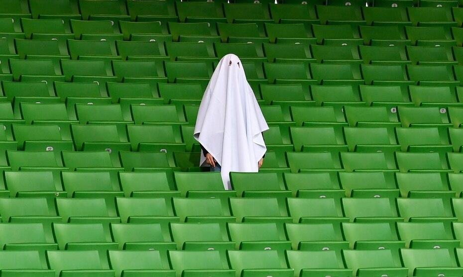 Un hombre vestido como un fantasma de pie en una tribuna vacía antes del partido de ida de los octavos de final de la Liga Europa entre Linzer ASK y Manchester United en Linz, Austria, en esta fotografía de archivo del 12 de marzo de 2020. El partido se jugó en un estadio vacío.
