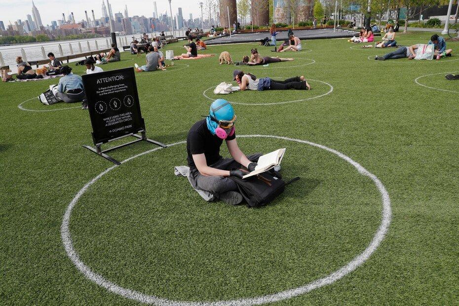 Ridley Goodside usa una cubierta de goma para la cabeza de buceo junto con gafas y una máscara especial de filtración de aire para protegerse de la propagación del coronavirus mientras se sienta en un círculo designado marcado en el césped en el Domino Park de Brooklyn.