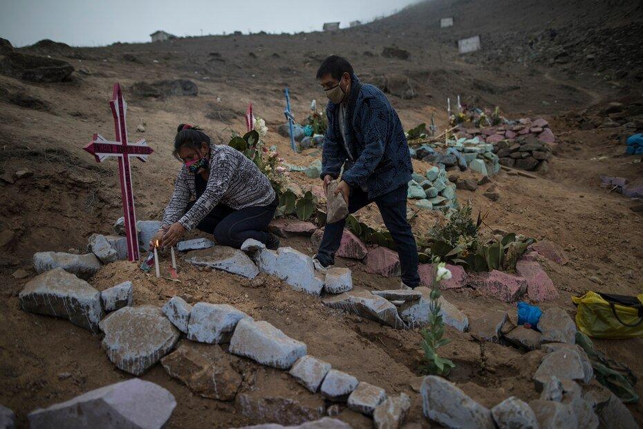 Los hermanos Julia y Jorge López decoran la tumba de su madre, quien recientemente falleció por el nuevo coronavirus, en un cementerio público en Lima, Perú, el viernes 22 de mayo de 2020. A pesar de las estrictas medidas para controlar el virus, esta nación sudamericana de 32 millones se ha convertido en uno de los países más afectados por la enfermedad.