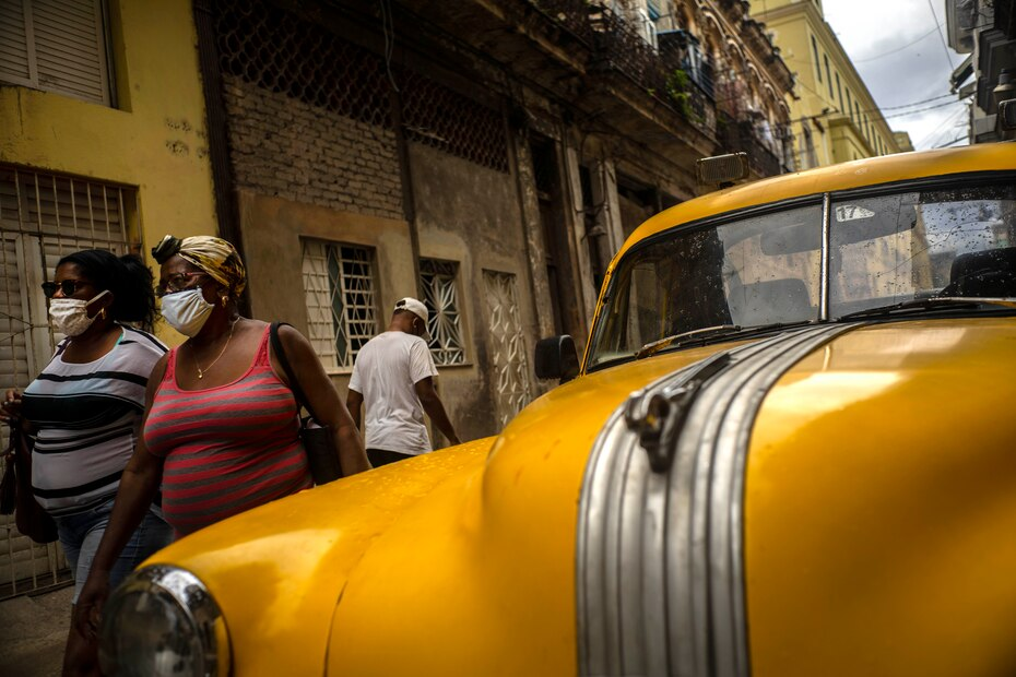 Mujeres con máscaras contra la propagación del nuevo coronavirus caminan por una calle en La Habana, Cuba, el lunes 25 de mayo de 2020. Las autoridades cubanas exigen el uso de máscaras para cualquier persona fuera de sus hogares