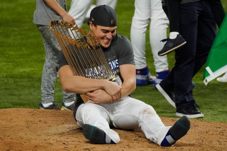 El puertorriqueño Kike Hernández abraza el trofeo de Serie Mundial sentado en la loma del Globe Live Field.