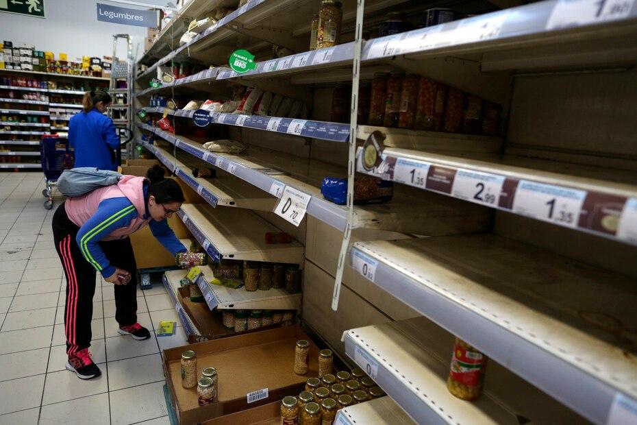 Una compradora sostiene un artículo rodeada de estantes casi vacíos en un supermercado en Madrid, en esta fotografía de archivo del 10 de marzo de 2020. La gente hizo compras de pánico de alimentos y suministros después de que el ministro de Salud de España anunciara un fuerte aumento en los casos de coronavirus en la capital nacional y sus alrededores.