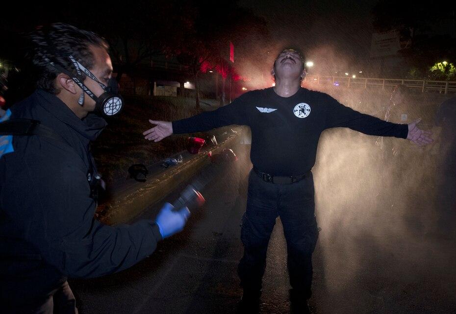 En esta imagen del 30 de mayo de 2020, Óscar Becerril, coordinador de paramédicos, desinfecta a su colega César Ávila después de salir a recoger a un paciente enfermo de COVID-19 desde su base en Iztapalapa, una demarcación de la Ciudad de México.