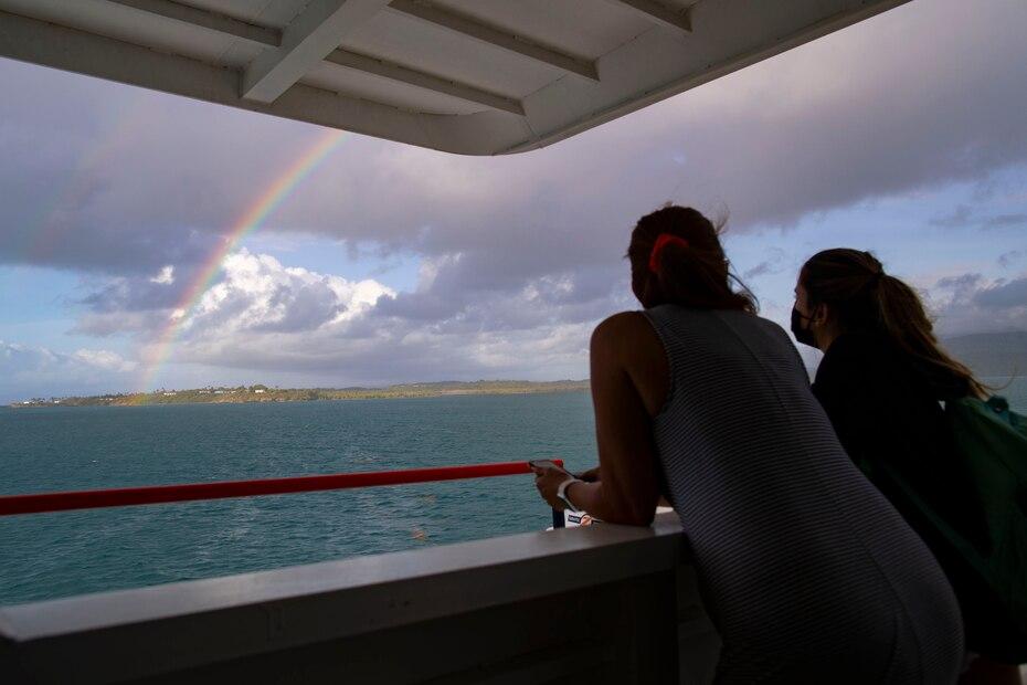 Dos personas observan un arcoiris que se formó mientras se realizaba la travesía hacia Vieques.