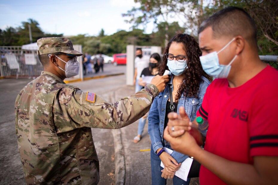 Un soldado de la Guardia Nacional le toma la temperatura a una pareja antes de hacer su entrada a la escuela María Simons de Rivera, donde recibirían la vacuna de Moderna.