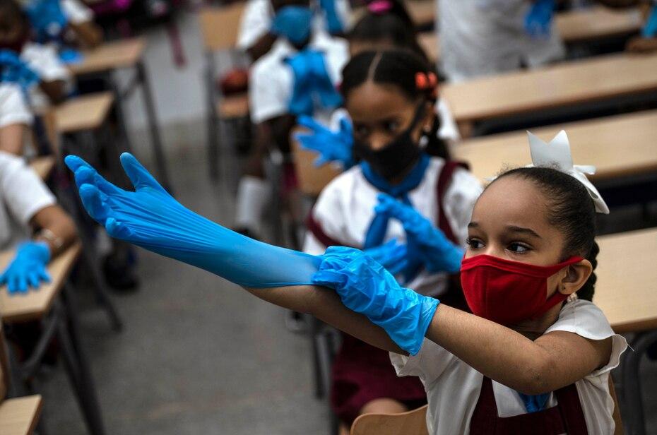 Con una máscara como medida de precaución en medio de la propagación del nuevo coronavirus, una niña se pone guantes de plástico durante la clase en La Habana, Cuba, el lunes 2 de noviembre de 2020. Decenas de miles de escolares regresaron a clases en el mes de noviembre en La Habana por primera vez.
